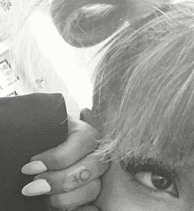 Venus symbol tattoo on Ariana Grande's right ring finger.