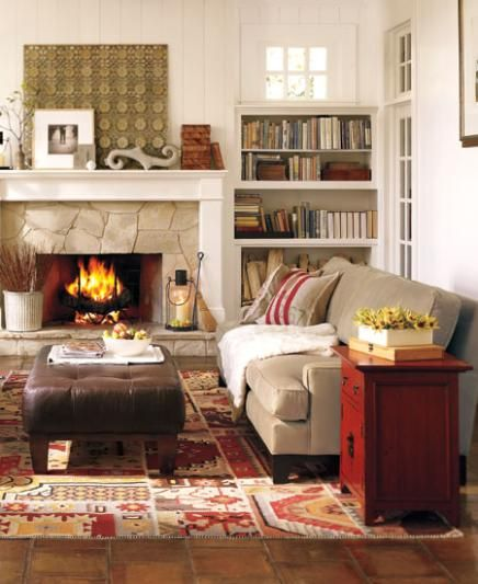 COUNTRY LODGE LIVING ROOM  Designers agree that every room should have a dash of red. Here, a hand-distressed red side table illustrates just why this is true, creating instant energy amid the otherwise neutral-toned furniture. Grounding the room in color and warmth is a boldly patterned rug in fiery autumn hues.  Benjamin Moore™ Paint Color:  OC-17 white dove