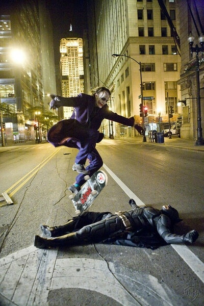 Heath Ledger (in full Joker drag) jumps a skateboard over Christian Bale (in full Batman drag.)