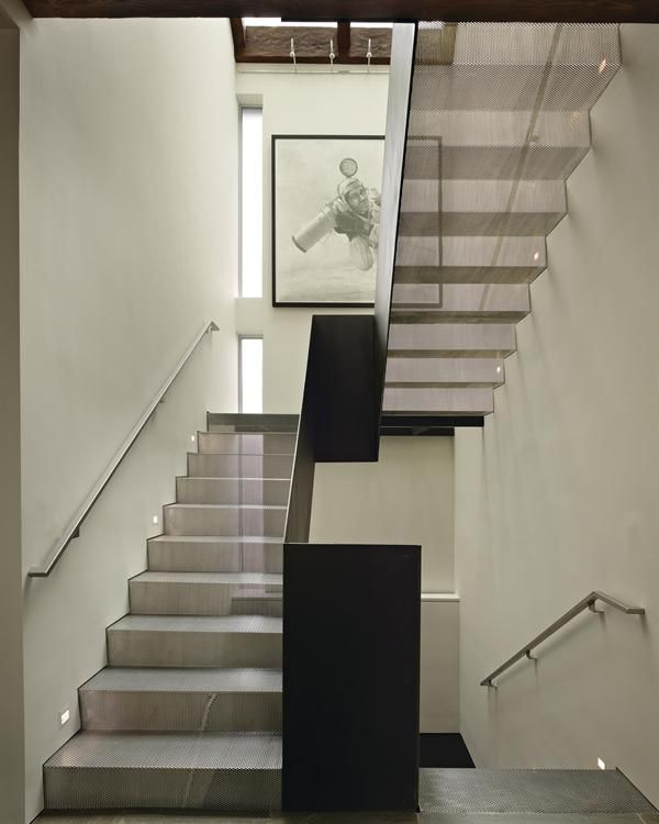 Stair runs fabricated from folded sheets of perforated steel filter light from a skylight above.