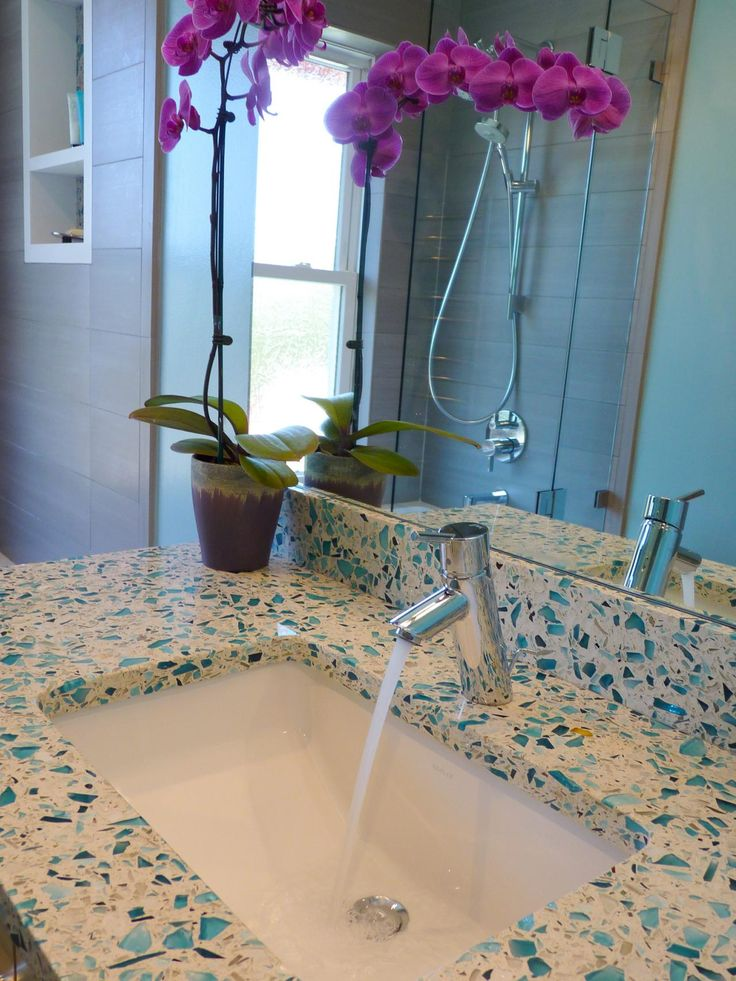 In this Caribbean-inspired bathroom, blues and grays are used to create a cool, relaxed atmosphere. The unique countertop is made from recycled glass.