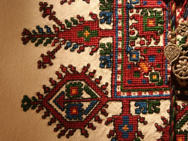 Detail from a Bosnian shirt showing cross stitch embroidery in geometric patterns of blue, red and green. From the Durham Gallery at Bankfield Museum. Copyright Calderdale.