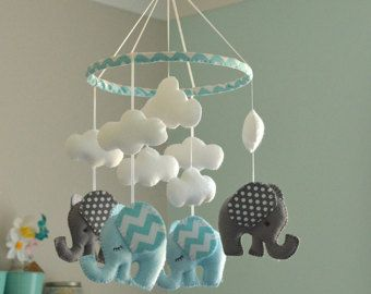 Welcome to Flossytot This Elephant Mobile is MADE TO ORDER This mobile consists of 4 elephants, made using premium wool blend felt in ice blue/aqua chevron and grey /grey chevron. Above each elephant is a cloud. Hanging in the centre is a hot air balloon using the same colours used on the elephants. These mobiles are original Flossytots designs and are carefully cut and handstitched with lots of care and attention to detail. They make a beautiful feature for a nursery or bedroom...