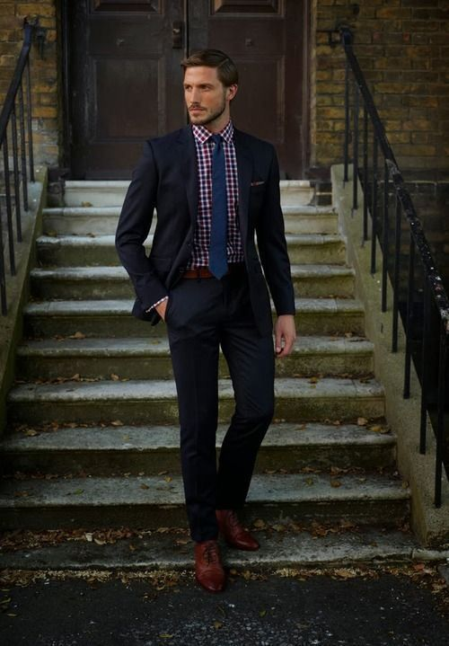 Shop this look on Lookastic:  http://lookastic.com/men/looks/dress-shirt-tie-belt-suit-oxford-shoes/6882  — Red and Navy Gingham Dress Shirt  — Navy Tie  — Dark Brown Leather Belt  — Black Suit  — Brown Leather Oxford Shoes