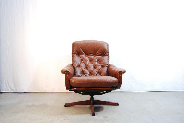 SOLD (Amsterdam) / Een mooie jaren 70 draaibare fauteuil van Göte Möbel Nassjo (G-Möbel) uit Zweden. Gebogen houten frame met een bruin gecapitonneerd leren bekleding en armleuningen. De stoel staat op een metalen stervoet welke…