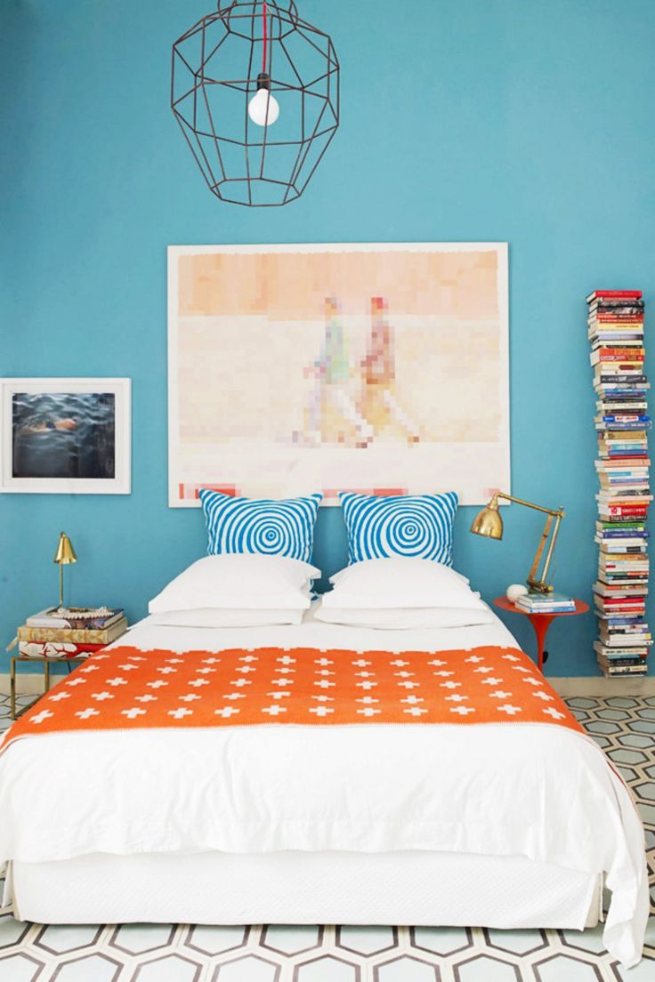 Bright blue bedroom with vintage tiled floors, a large metal pendant light
