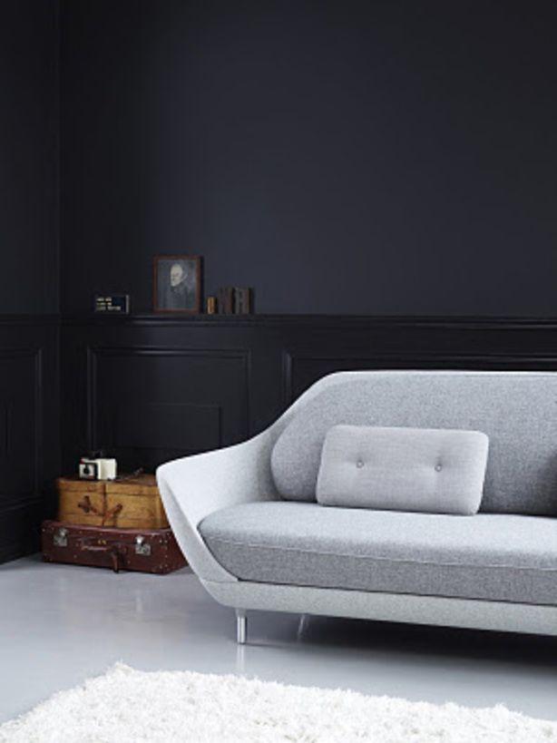 Lichte designbank in kamer met donkere muur.