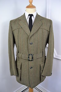 A VINTAGE 1960's DERBY TWEED 'NORFOLK' BLAZER.    Item Description:        A MEN'S UK LARGE 44 REGULAR FITTING (detailed measurements given below). Green colour. Three buttoned (all original). Collar button. Flapped and buttoned pockets at the waist. Removable belt. Single vented. Made from Derby Tweed. Green lining with two inside pockets. Single button cuffs. Made by Chris Davies in England. Genuine 1960's English vintage. Excellent condition. Dry cleaned and steam pressed before being…