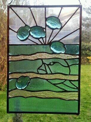"""Stained glass design called """"Brief Escape"""". I made this after finding the small glass fish in a garden centre. Seeing fish jump in this way is a sign of bigger fish below."""