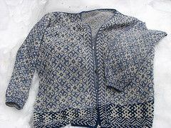 This is an all-over patterned cardigan pattern with 3 charts knitted in the round, with steeks in the front, in the neck area, and in the armholes. The lower edge is begun with PWYC (Purl While You Can). You can either mark the center-back stitch as the pivot stitch, so that as you knit across, when you hit the pivot stitch, you will read the chart in the reverse direction; or you can center each of the the 3 charts at the back and count toward the center-front. Short rows can be worked ...