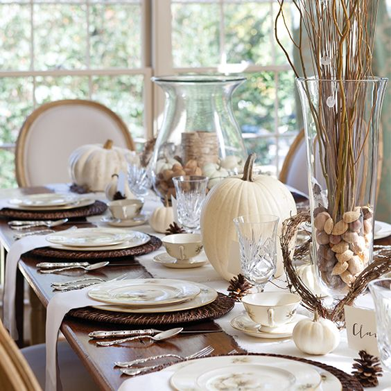 Shades of brown and white are a wonderful color palette for your Thanksgiving table. The colors, like the holiday, actually bridge the seasons of fall and winter. White pumpkins and small pinecones along with other natural elements such as dried sticks, birch-wrapped candles, and mixed nutscreatea casual yet elegant look. Large glass vases and hurricane lanterns