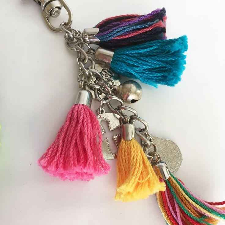 Llavero con cadena y mosquetón metálicos, dijes varios y flecos de hilo de distintos colores. Largo total del producto: 10 cm
