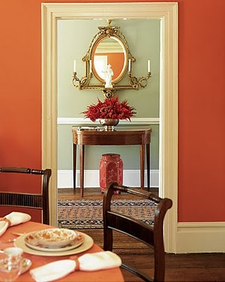 gorgeous dining room combination of orange / coral with a pale celery green and gold accents peeking in - love it!!!