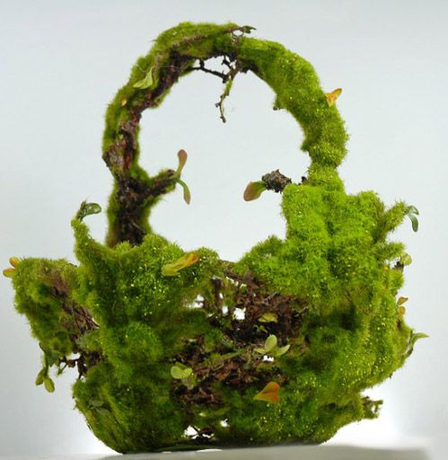 Artificial moss basket with a cream or white pillar candle in the center as a centerpiece for an event table.