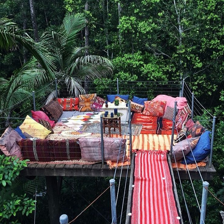 raised deck amongst the tree tops dressed with eclectic mix of rugs and cushions