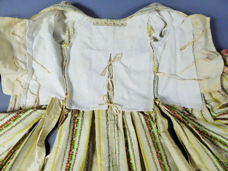 "Inside view, robe à la francaise, France, ca. 1760. ""Mexicaine"" silk taffeta with yellow stripes on cream ground alternating with stripes with small bouquets on light blue and cream ground, linen lining. Sleeve ruffles with pink trimmings."