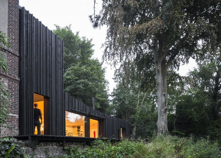 Blackened timber house extension in the forest by Marchi Architectes
