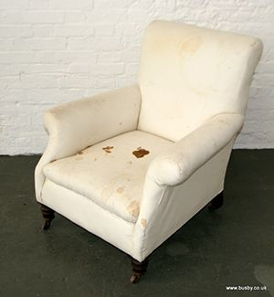 A late Victorian traditionally upholstered scroll back armchair.