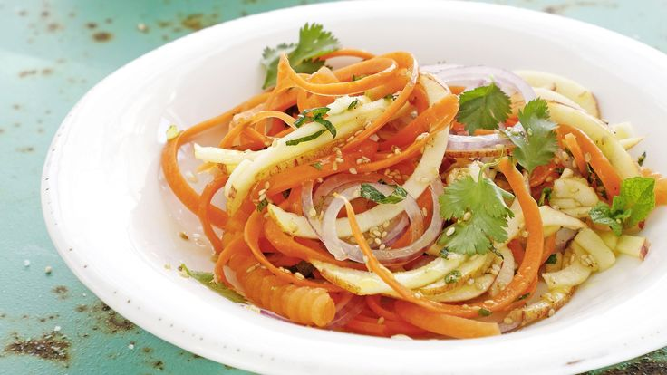 Wir essen auch mit den Augen. Etwa diesen Appetizer mit Karotten-Apfel-Spiralen. Für einen leckeren Asia-Touch sorgt das Sesamdressing mit Honig, Minze, Koriander.