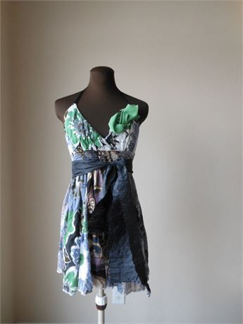 Tattered floaty flower print halter dress in soft cottonwith a wispy beach feel and a shabby bohemian style. Green, black, cream and gray print is perfect for walking the beach at night hand in hand. Has green asymmetrical tattered trim at the neckline and a black tie. Eco friendly summer fashion or bridesmaid, evening or party gown.   Soft cotton gown in floaty flower print with a soft spring green asymmetrical tattered detail at the front neckline. Has an a comfortable shirred elasticized…