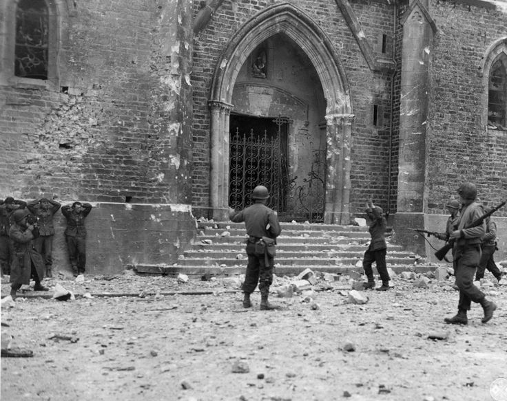 Soldiers of the 121st Infantry Regiment, 8th Infantry Division, U.S. and German prisoners at the Cathedral in the French town of La E-du-Puy (La Haye-du-Puits).