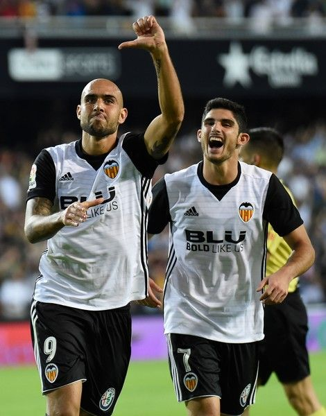 Valencia's Italian forward Simone Zaza (L) celebrates with Valencia's Portuguese midfielder Manuel Guedes after scoring a goal during the Spanish league football match Valencia CF vs Sevilla FC at the Mestalla stadium in Valencia on October 21, 2017. / AFP PHOTO / JOSE JORDAN