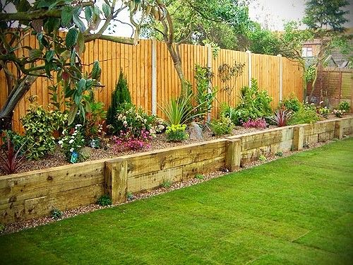 Raised flower bed along fence garden along fence yards for Garden decking borders