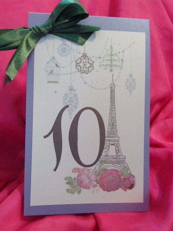 """Numar de masa""""Paris, mon amour"""", ideal pentru nuntile avand drept tema """"Calatoriile"""". Este realizat din carton sidefat lila, una dintre culorile Pantone pentru primavara 2015. Eticheta pe care est..."""