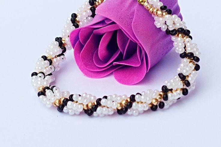 Černobílá elegance Elegantní náramek z rokajlu navlékaného na vlasec v univerzální černobílé barvě. Pokud máte ráda elegantní styl podtržený zlatou barvou, je to kousek pro Vás. Délka náramku je 21 cm se zapínáním. Pokud by jste si přála tento náramek v jiných barvách, lze nechat zhotovit za stejnou cenu cca do sedmi dnů.