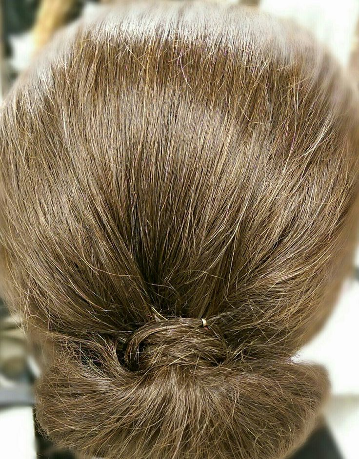 This updo known as the chignon starts with a sleek ponytail. To get the desired sleekness, a smoothing serum will be beneficial. Then a piece of hair wraps around the ponytail and is secured in place using a pin. The hair is then wrapped under the ponytail, secured, and fanned to either side to create the desired updo. To add volume to the crown and top of the head, a backcombing brush and some volumizing product would be beneficial.