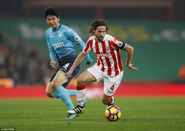 Joe Allen, another Stoke player who used to play for Swansea, attempts to get away from Ki Sung-yueng in midfield