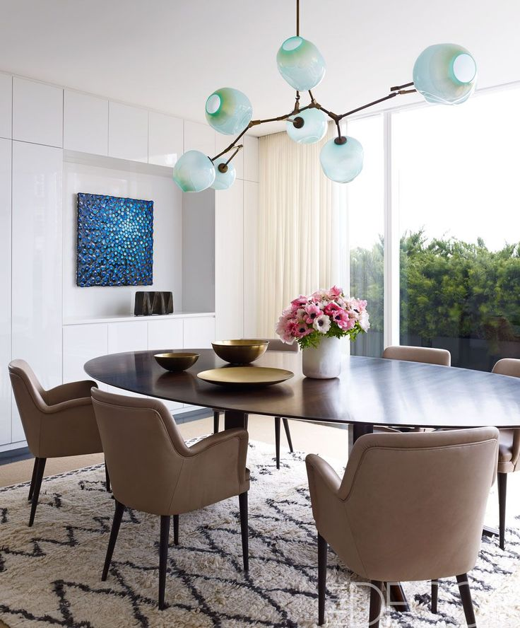 A set of 1954 chairs by Osvaldo Borsani surrounds the custom-made dining table; the light fixture is by Lindsey Adelman, and the painting is by Robert Melee.   - ELLEDecor.com