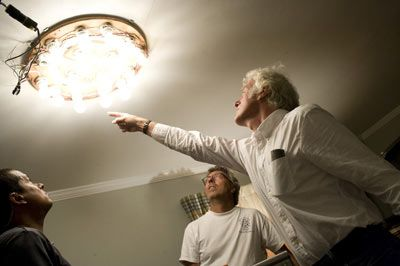 Deakins works with O'Leary (center) and electrician Scott Gregoir to fine-tune a ringlight comprising 60-watt bulbs that acted as an overhead source in the house.