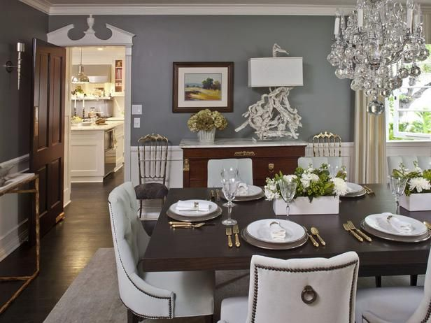 Gray walls in this traditional dining room contain a hint of Wedgwood blue, adding to the elegance of an already-sophisticated space. Lighting in the room is traditional with an edge, including a show-stopping crystal chandelier with oversized orbs and a gnarled driftwood table lamp.