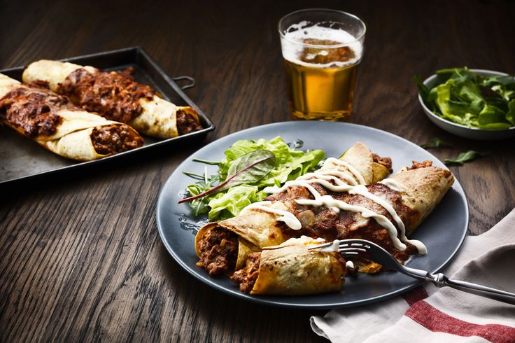 Een in de oven gegratineerde maistortilla met vlees, uien en bonen, een milde tacosaus.