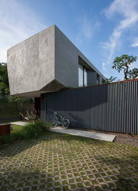 Corners appear to have been sliced away from the cantilevered concrete upper floor of this house in Indonesia