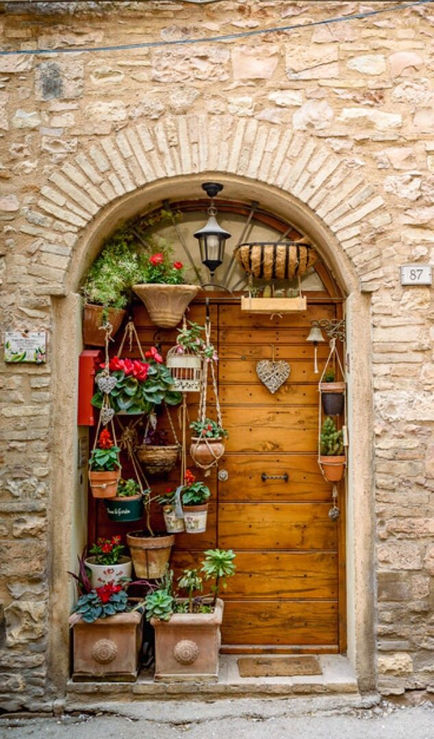 Door decorated with potted plants in Spello, Perugia, Italy.