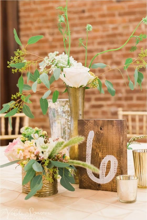 How to do a wedding reception with rustic industrial flair: hand-painted pale pink table numbers, loose, natural floral arrangements in a variety of containers. // Del'avant Event Center | Noble Sparrow Photography