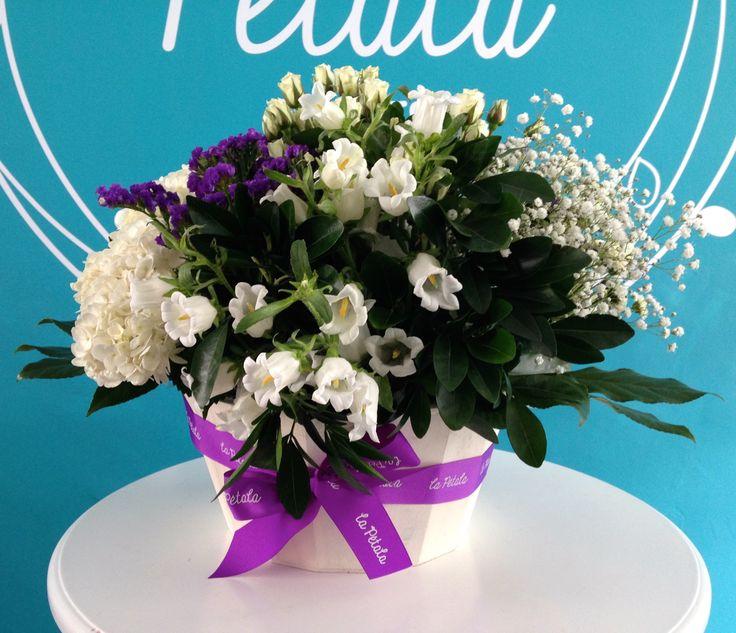 Despedida: Un arreglo lleno de esperanza.  Compuesto de flores blancas y moradas, dependiendo de las flores de temporada.  Solicítalo ya: Teléfono +571 2159030 o al correo electrónico clientes@lapetala.com.                Precio: $160.000