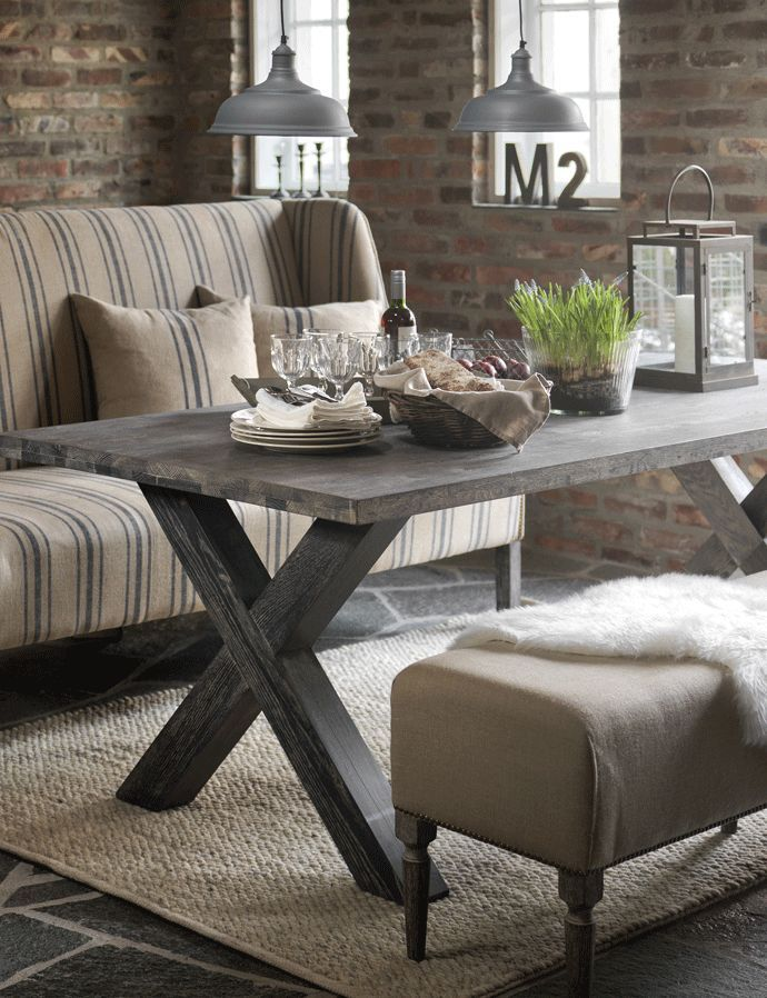 Rustic French Nation...dwelling area...blue & cream striped couch...weathered wooden desk...textured rug...previous brick wall & industrial metallic lights.