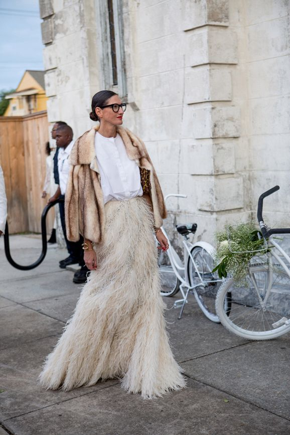 Jenna Lyons in a camel mink coat, floor-length cream feather skirt, a white button down, and her signature glasses at Solange Knowles wedding.