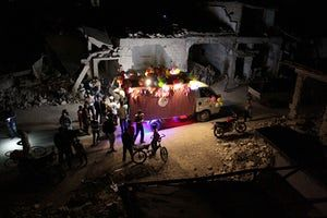 Syrians gathered around an ice-cream vehicle amid destroyed buildings, on the last day of Ramadan