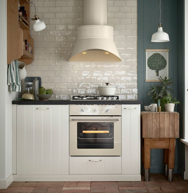 Beige Extractor Hood And Oven In An Off White Kitchen With Black Worktops  And White Porcelain Handles.