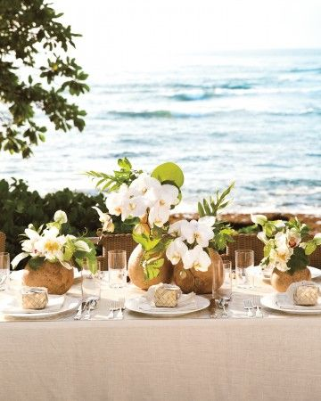 "This tablescape is breathtaking enough to draw eyes away from its scenic backdrop. Even better, it's a cinch to put together (the vessels are lightweight and ship anywhere affordably). We turned cut gourds into all-natural vases, filling them with phalaenopsis orchids and tropical leaves. Letting them take center stage, we set the rest of the table with simple glasses and silverware atop a breezy linen tablecloth. The Details: Gourds, $11 each; amishgourds.com. ""Top Class Beverage"" glas..."