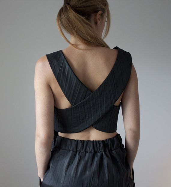 הגרסה שלי לשמלה-הקטנה-השחורה היא בעצם סט של חולצה וחצאית שמשלב חזית מחויטת לצד מחשוף ממזרי בגב עם רצועות מצטלבות.  הסט עשוי מאריג פליסה שחור, במראה מקומט ומעט מבריק, בהשראת סינרים יפניים (והמעצב הדגול איסי מיאקי....).  החולצה א-סימטרית: החלק הקדמי ארוך יותר ומצויד במתפרים מחמיאים באזור החזה והיא נלבשת ללא כפתור או רוכסן (שאגב, מסתירים את קו החזיה).  ניתן ללבוש את החלק העליון מעל גוזייה צבעונית, גופיה צמודה אבל הכי כיף ללבוש אותו בגב חשוף.... לחצאית גומי בחגורה בחלקה האחורי וכיסים נסתרים ...