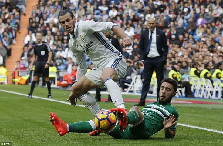 Gareth Bale challenges Leganes midfielder Unai Lopez for the ball while Real Madrid manager Zinedine Zidane watches on