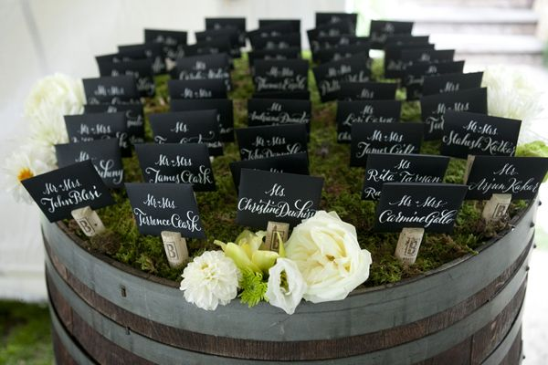 Wine corks used for seating chart. Love how they are displayed on the top of a wine barrel with a woodland theme.