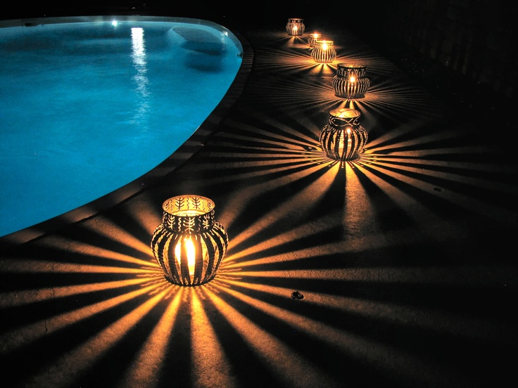Upcycled coffee can luminaries:  Pool side.