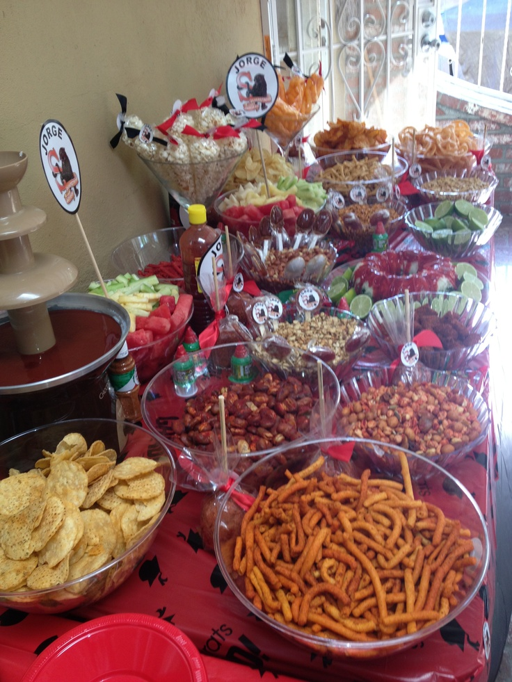 Graduation chamoy dessert table with peanuts, sabritones, duros, chips, fruit, chamoy apples, pelones