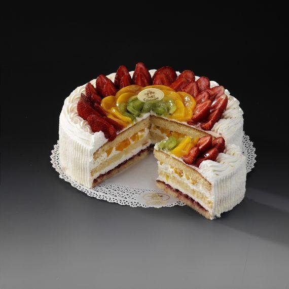 Tort Janek Krążki ciasta biszkoptowego przekładane śmietaną oraz kawałkami brzoskwiń. Dolny biszkopt posmarowaliśmy konfiturą z borówki. Do dekoracji użyto świeżych owoców.